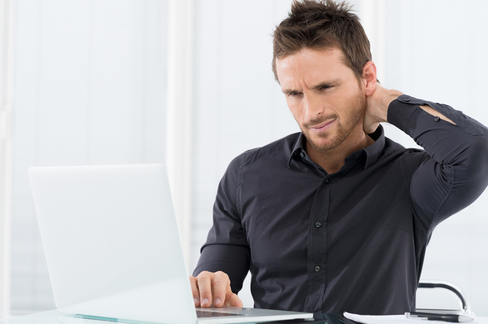 Man sitting at his desk with neck pain